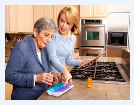 Caregiver with her mother reading pill box