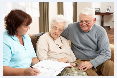 Elderly couple talking to home health aide