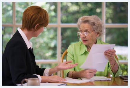 Elderly woman going over papers with consultant