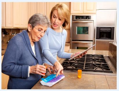Elderly woman and caregiver with pillbox