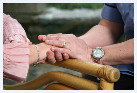 Elderly couple touching hands