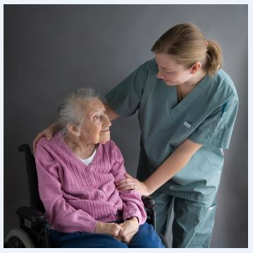 Woman in a wheelchair looking up at uniformed caregiver