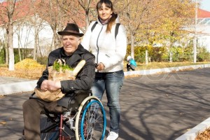 8065117-woman-helping-her-senior-handicapped-father-pushing-him-along-the-street-in-his-wheelchair-as-they-return-from-doing-his-grocery-shopping